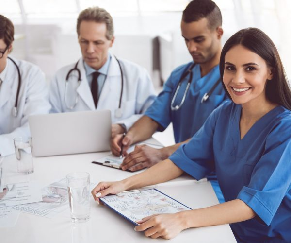 Successful medical doctors are using a laptop and discussing documents during the conference. Beautiful female doctor is looking at camera and smiling