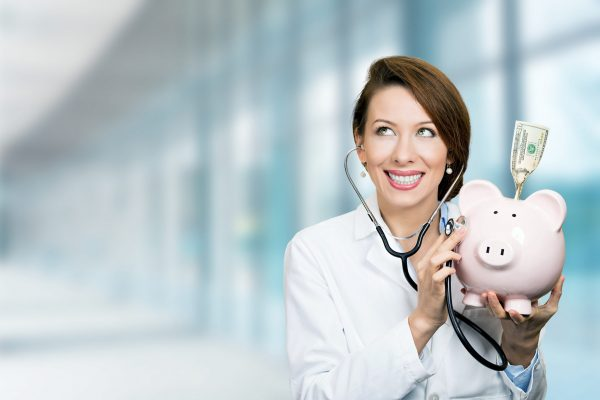 Portrait happy smiling female doctor holding listening to piggy bank with stethoscope standing in hospital hallway on clinic office windows background